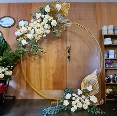 Golden hoop arbor with white florals and gold palm leaves.