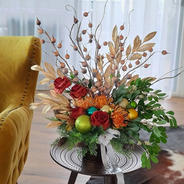 Christmas arrangement in warm colours. Fantasy sprays in cream and gold, green mistle toe, burned orange roses, orange pincushions and baubles.