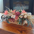 Table arrangement in natives. Blush pink and cream proteas and eucalyptus