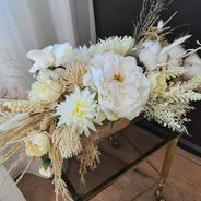 Faux flower dining table arrangement. Ivory roses, ivory natives, ivory wheat spray. cream chrysanthemum, bunny tales and grasses.