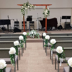 Chair pews. Champagne hydrangeas and greenery and ivory ribbon.