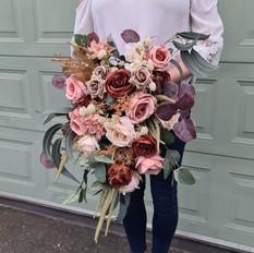 Faux flower cascading bridal bouquet in warm tones.