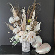 White faux flower and preserved flower arrangement.