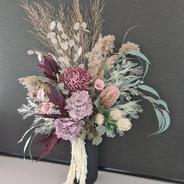 Large mauve arrangement in vase. Mauve peonies, dollar spray, mauve chrysanthemums, mauve banksia, fernspray , pampas, eucalypurs and hanging amaranthus.