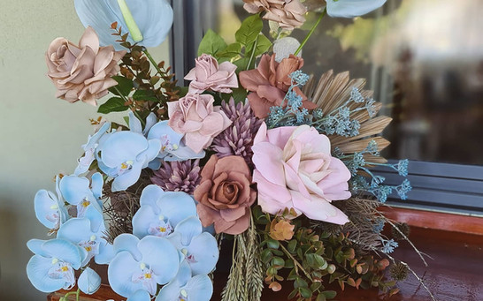 Arrangement in coffee and pale blue faux orchids.