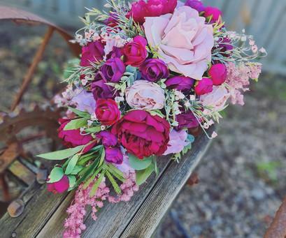 Faux flower teardrop wedding bouquet in maroon.