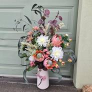 Large faux flower arrangement in vase. King proteas, white dahlias, burgundy gum leaves, pink thistle, pink flower buds, white wattle and gum leaves.