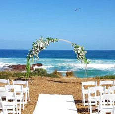 Wedding arch with Proteas, white reflexed roses, and greenery.