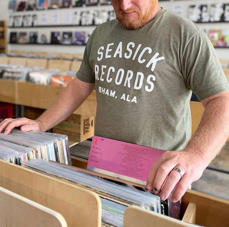 Man browsing through records at Seasick Records store. Is sporting an olive green Seasick Records t shirt