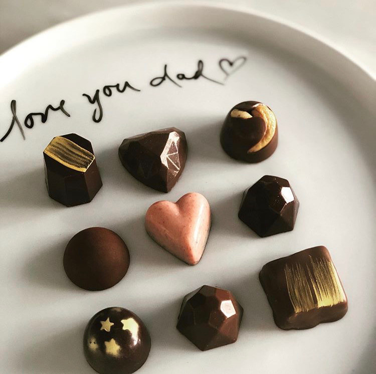 a set of nine scrumptious chocolate bon bons on a white plate with the words 'love you dad' written in chocolate.