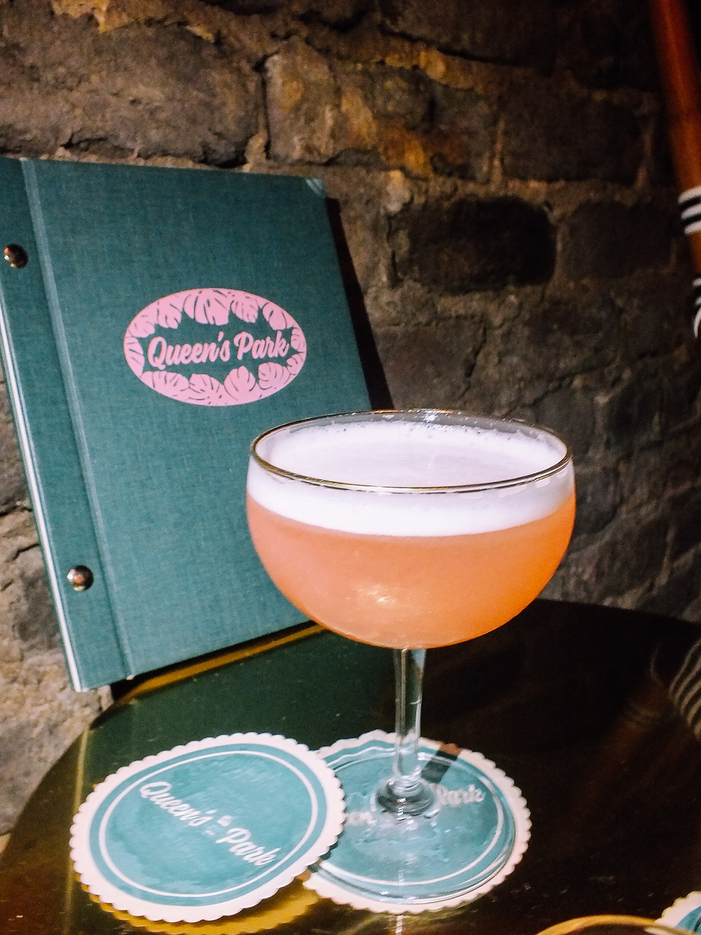 Queen's Park teal and pink menu behind a pink cocktail, called the Clover Club