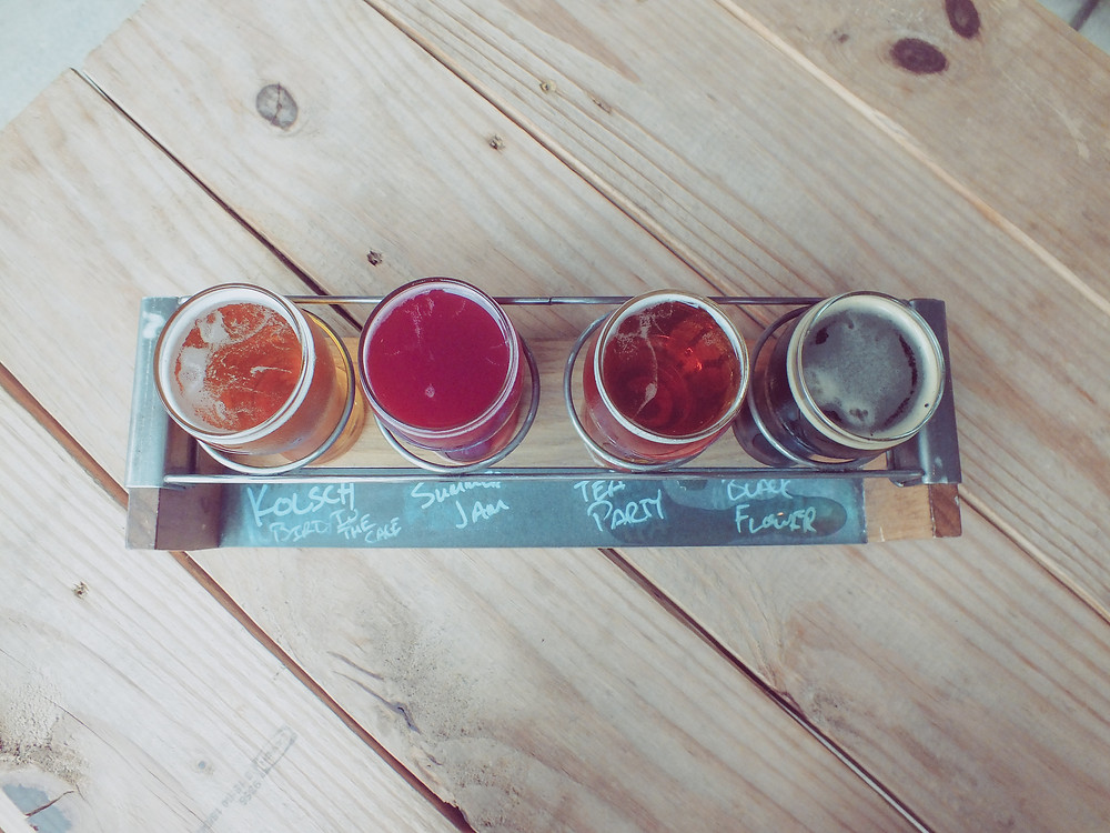 a flight of beer, four mini glasses of beer on a wooden plate at Birmingham District Brewing.
