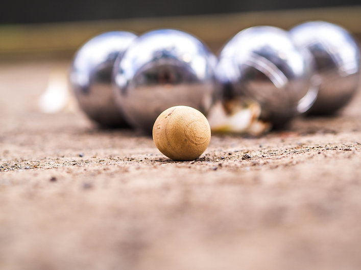 Four metallic petanque balls blurred and