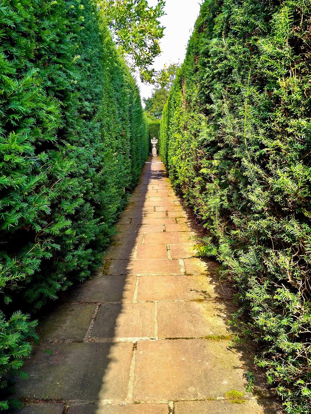 Statuary amidst tall hedges at Sissinghurst Castle