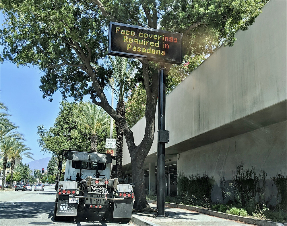 """Street sign saying """"Face coverings Required in Pasadena"""""""