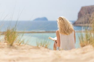 Photo of woman on beach reading from Wix/Bigstoc
