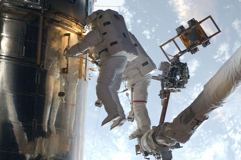 Travaux de maintenance sur le HST lors de sa dernière mission de service de 2009, par les astronautes John Grunsfeld et Andrew Feustel. Le HST est à gauche de l'image, les astronautes accrochés aux mains courantes et au bras de la navette, qui apparaît à droite. Image : NASA.