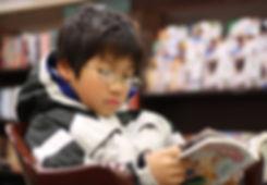 Young_boy_reading_manga.jpg