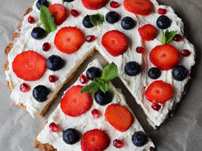 Keto almond flour tart topped up with whipped cream and berries.