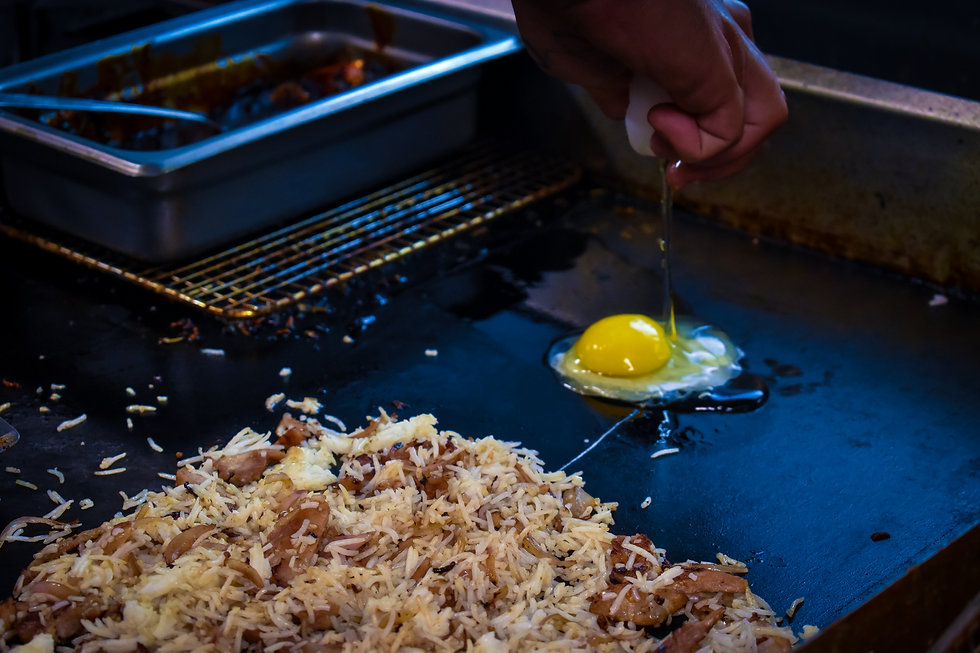 Chef Keith cracks an egg on a flat top grill behind pork fried rice.