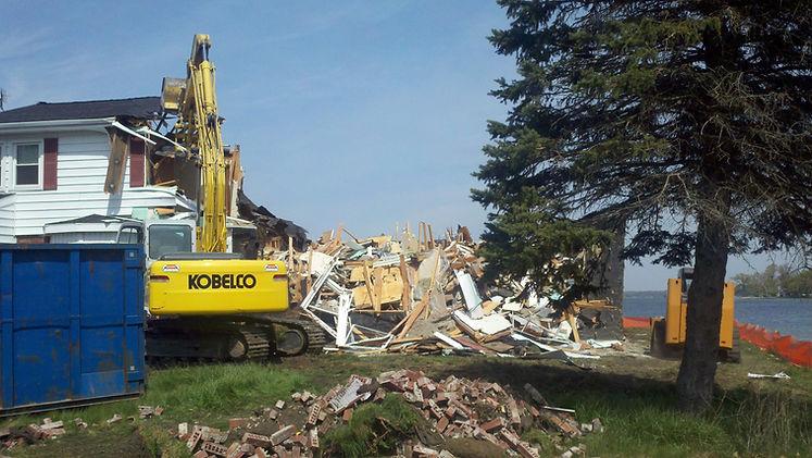 Excavator demolishing a house
