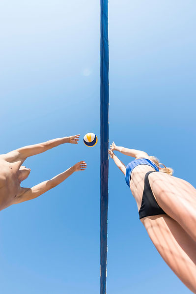 low-angle-volleyball-players-reaching-ba