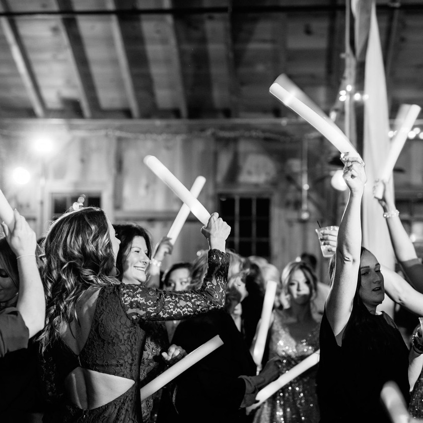 wedding guests dance while holding up glow sticks