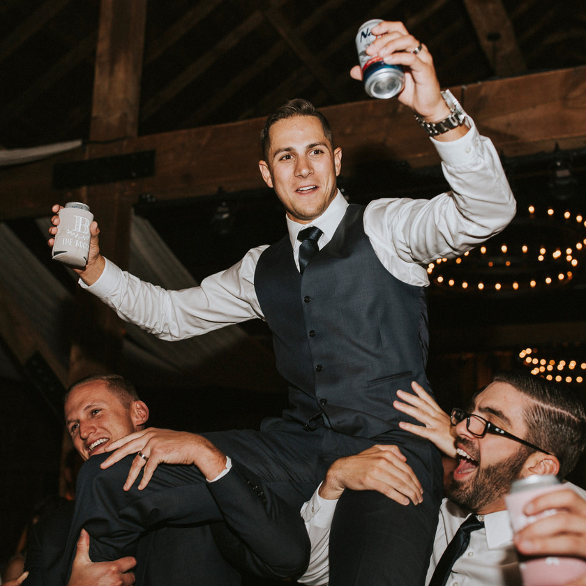 groom double fisting beer while on friends' shoulders