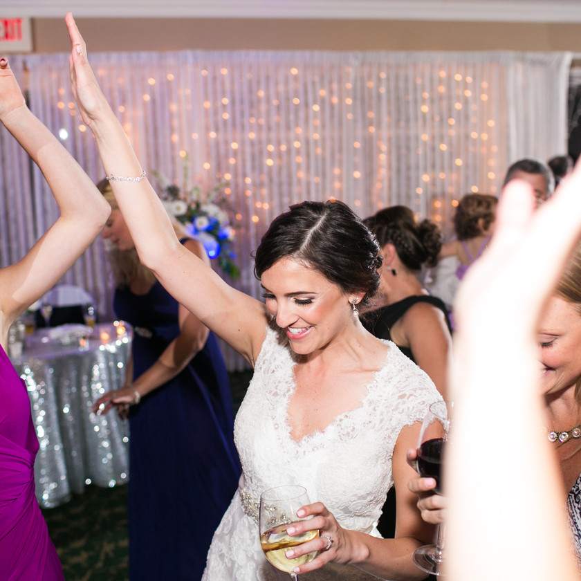 bride and guests dancing with hands up
