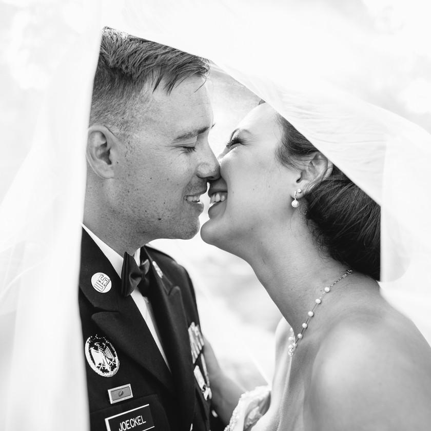 bride and groom kiss underneath veil