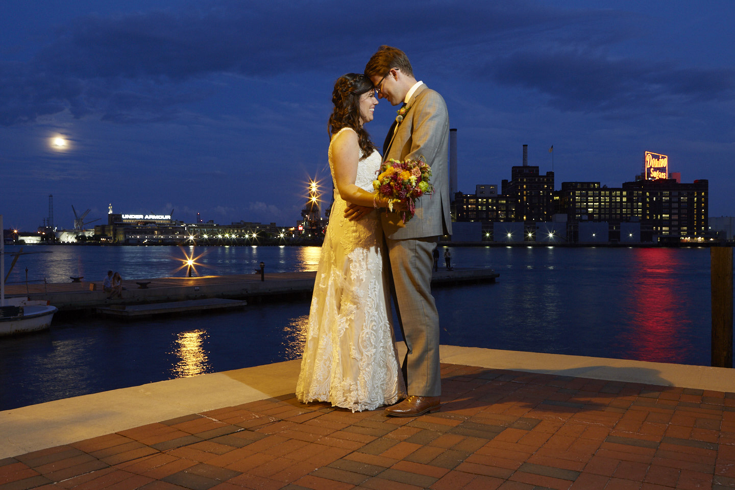 bride and groom stand together by the water in the city