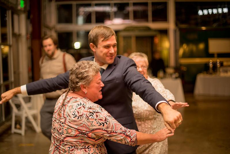 groom dances between two older women