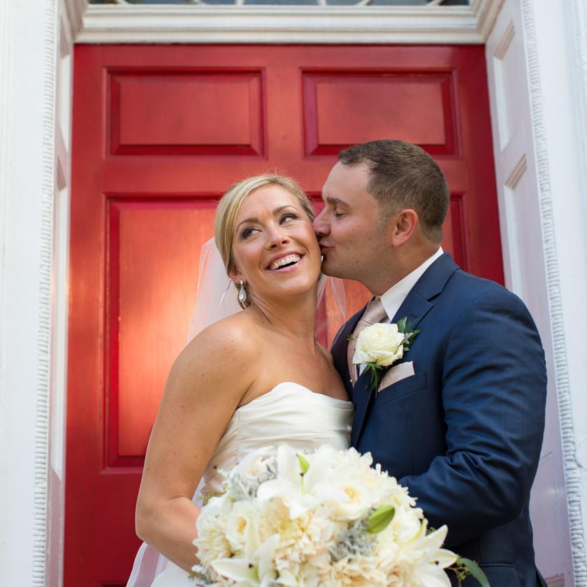 groom kisses bride's cheek in front of red door