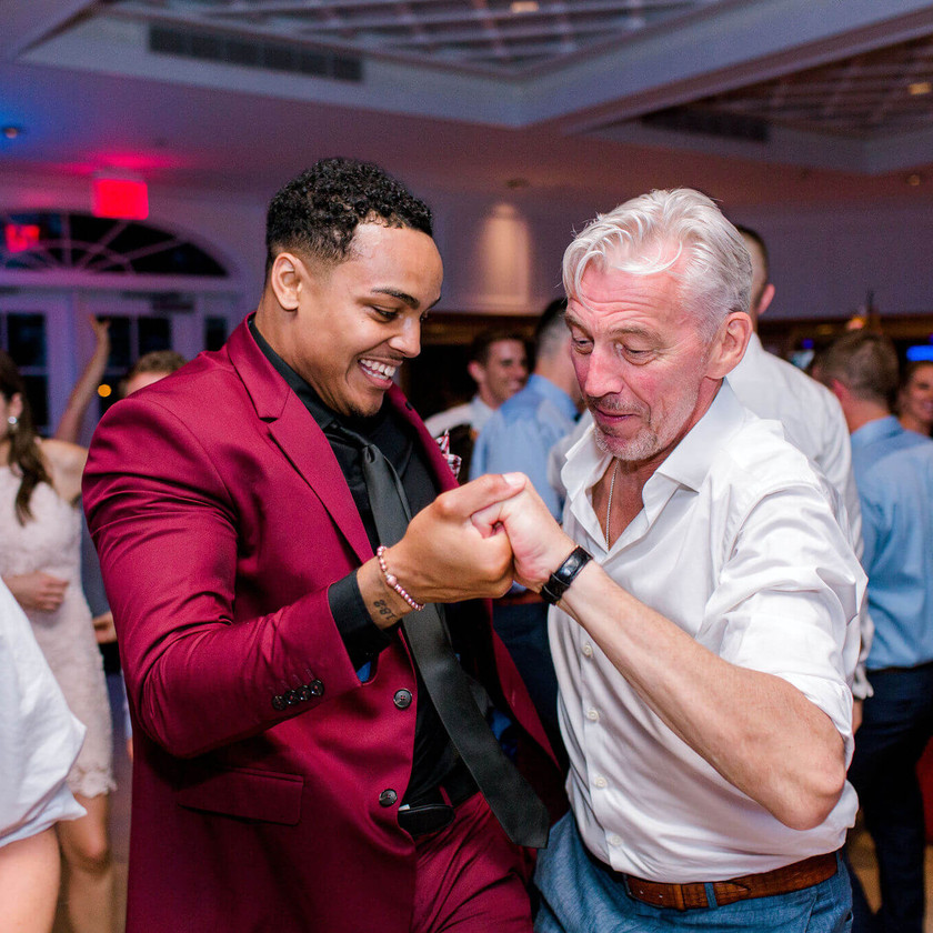 young man in red suit dancing with older man