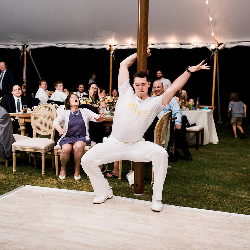 guy dances up against tent pole