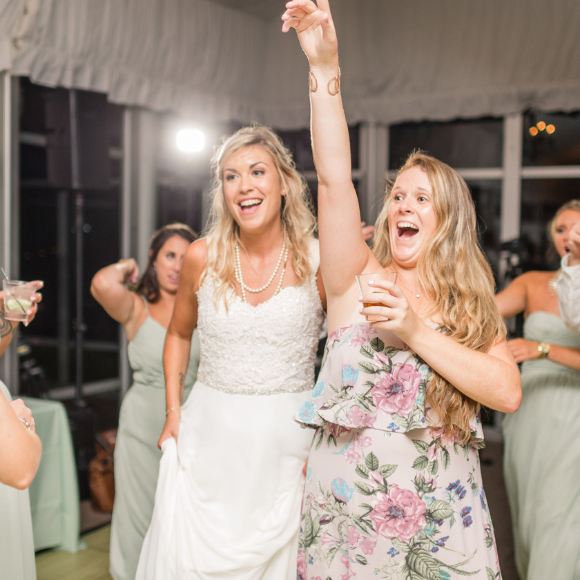 woman has hand up while partying with bride