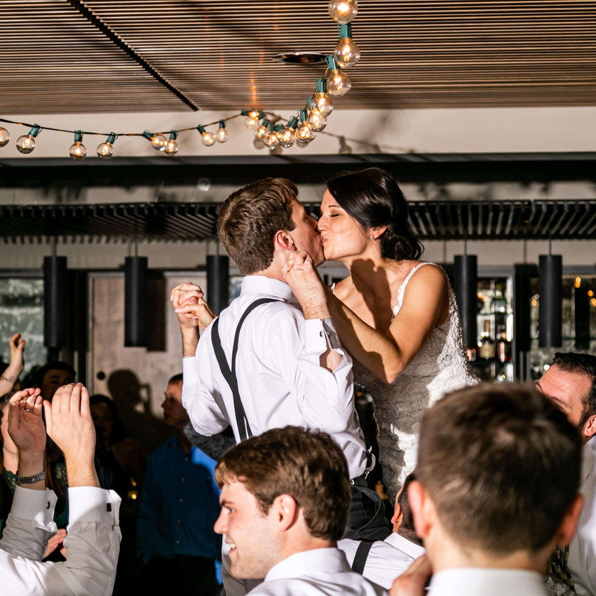 bride and groom kiss while lifted up over wedding crowd