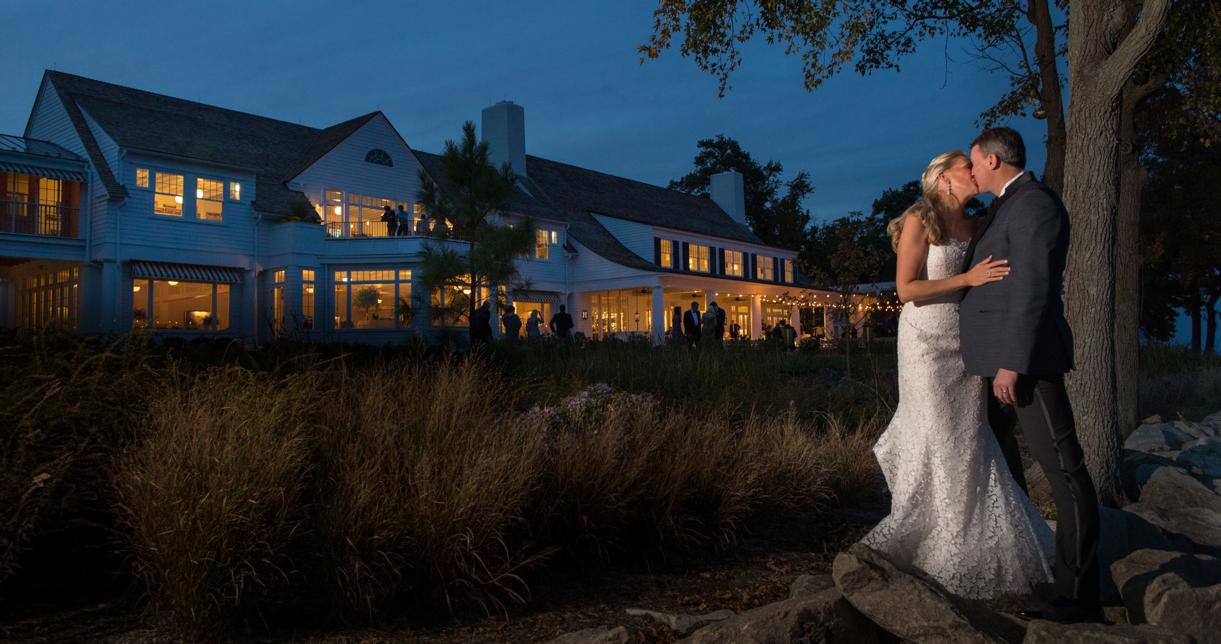 bride and groom kiss underneath tree with gibson island club in the background
