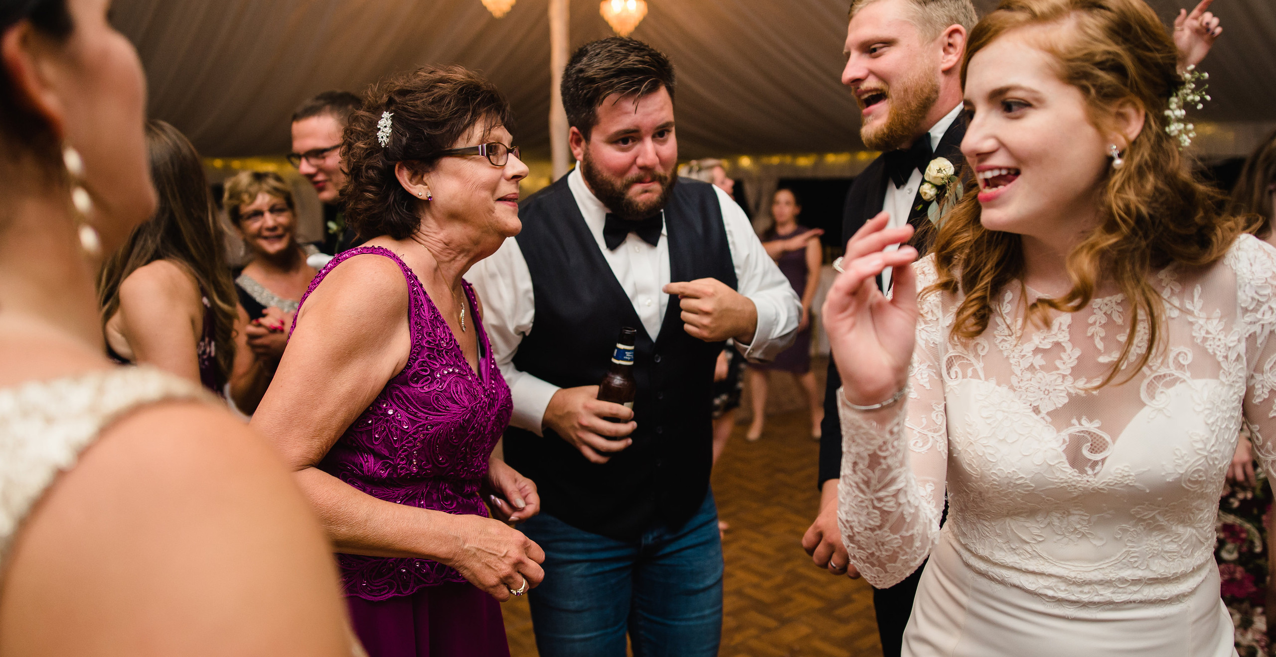 bride and groom dancing with family at wedding
