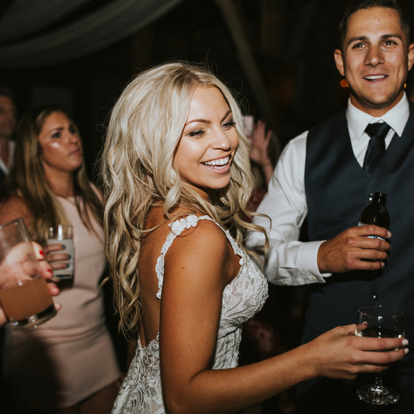 bride and groom dancing with drinks in hand
