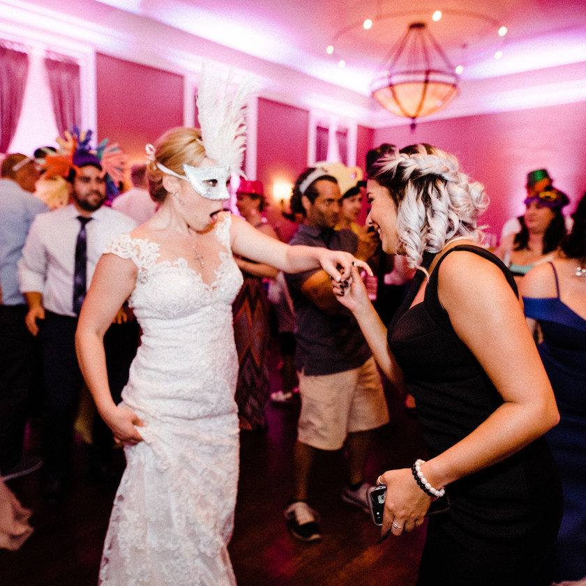 bride wearing mask dancing with wedding guests