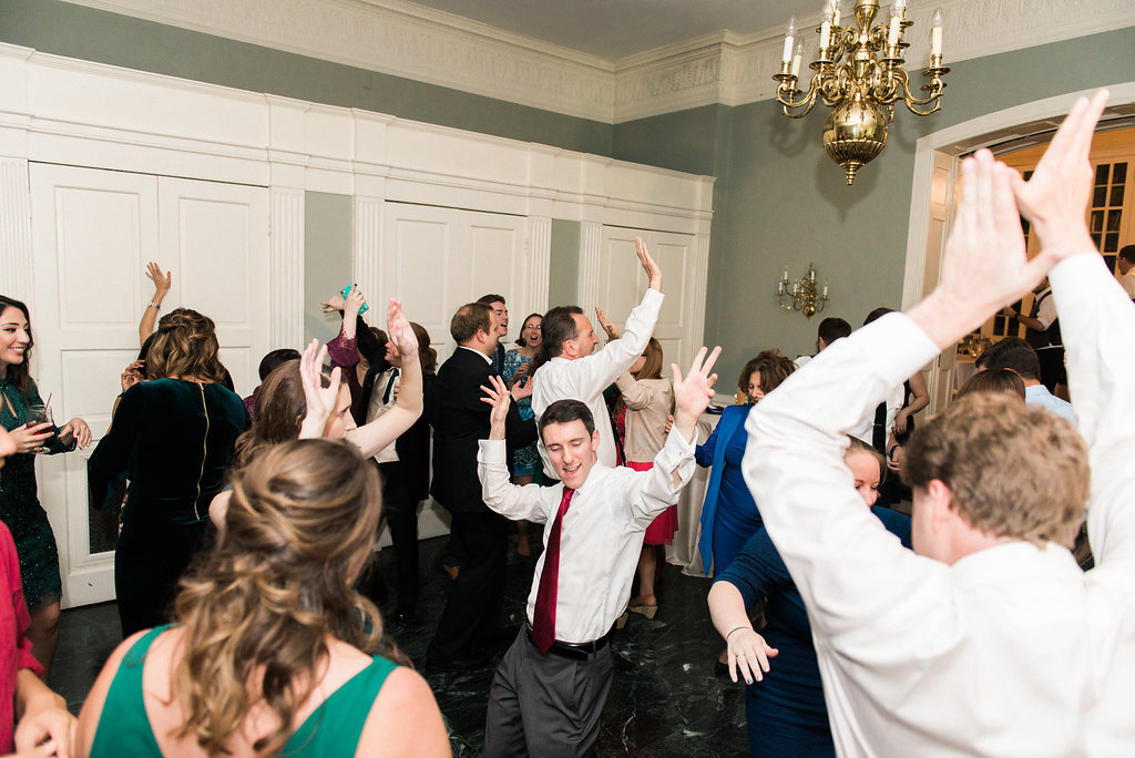 guests dance with hands up at wedding