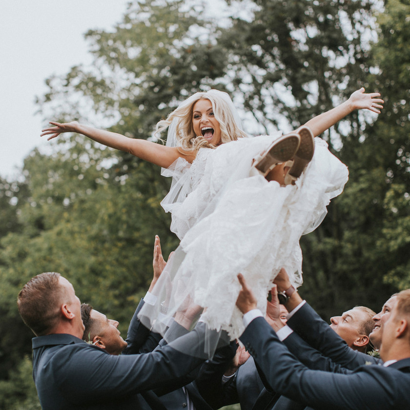 groomsmen tossing bride up in the air