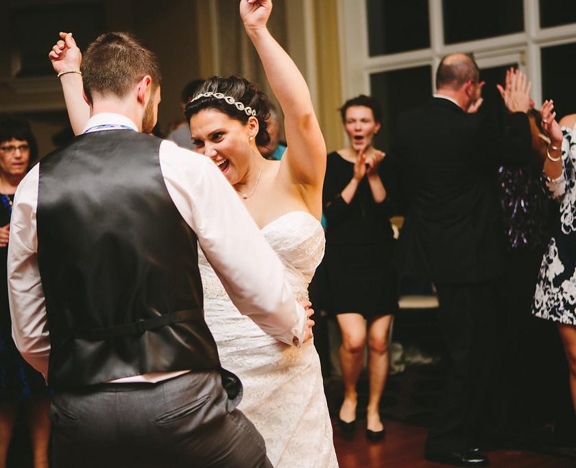 bride dances with hands up with groom