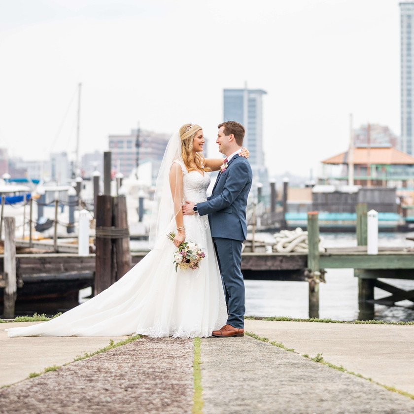 bride and groom pose on baltimore waterfront