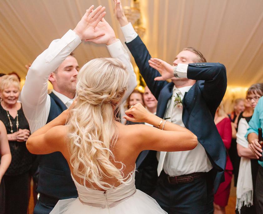 bride, groom and friends dance