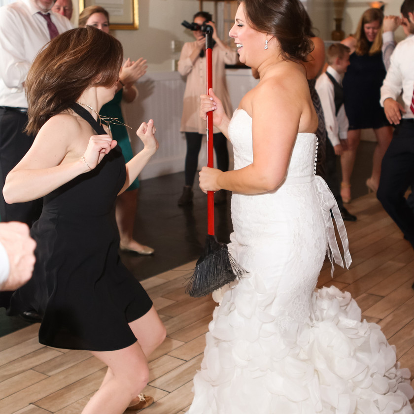 bride dancing while holding broom