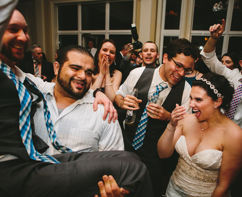 bride laughs watching guy carry her husband while dancing