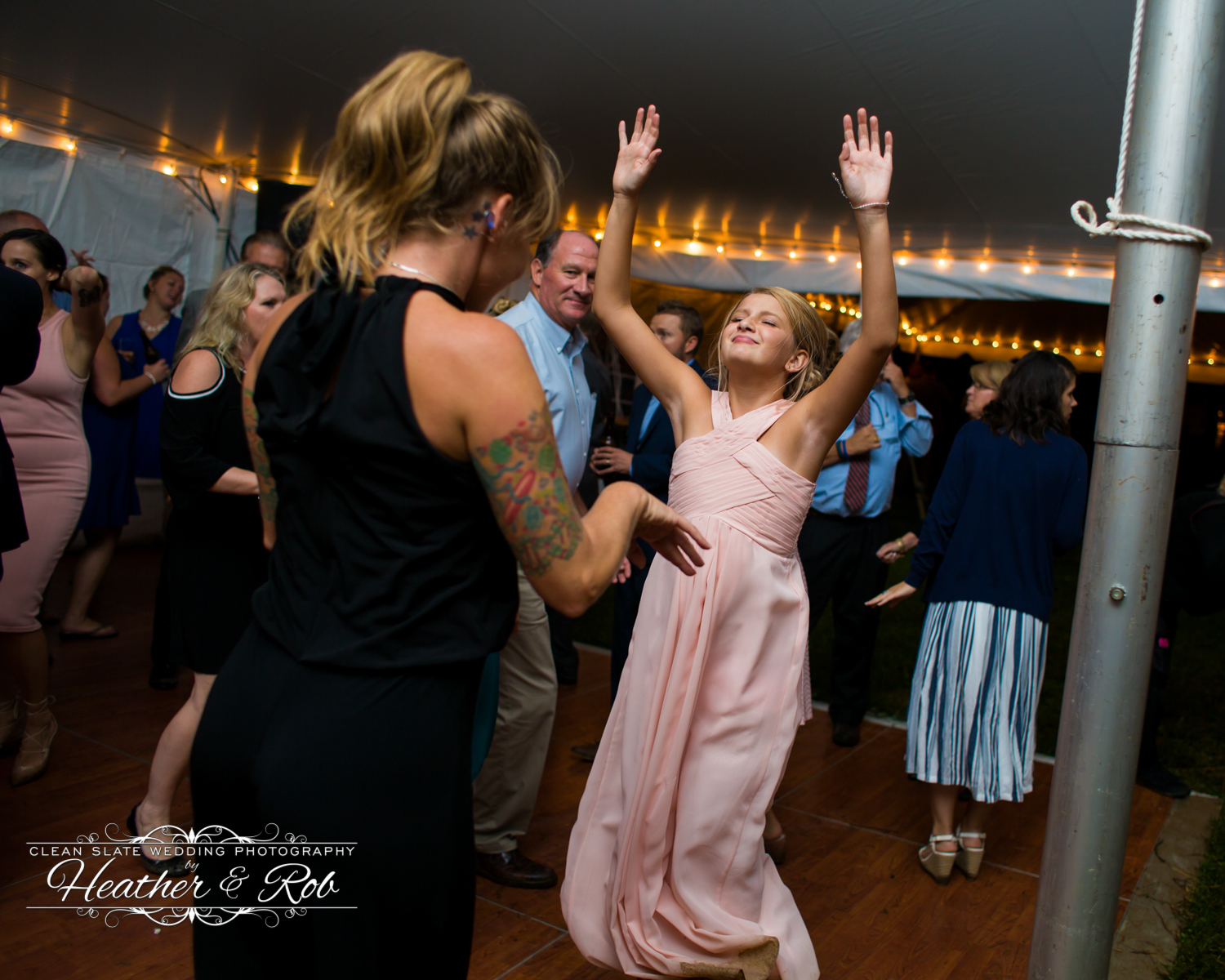 young woman dancing with hands up at wedding