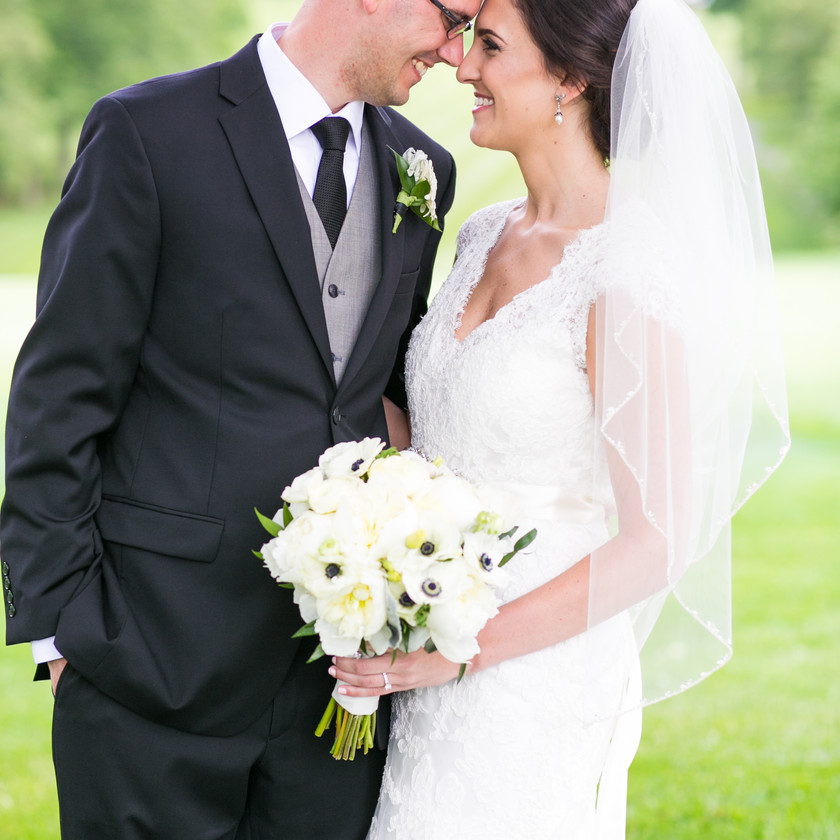 bride and groom smile towards each other